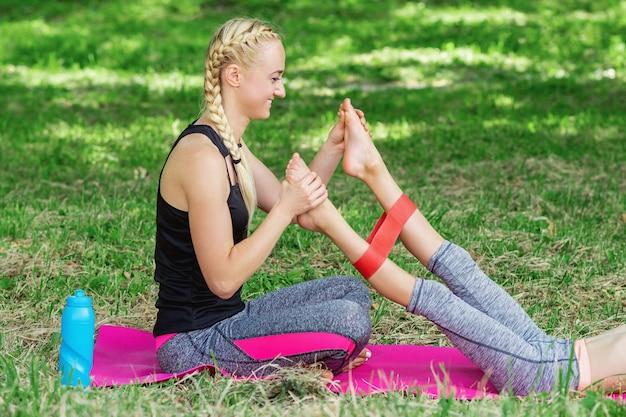 Молодая женщина тренирует ноги маленькой девочки резинкой фитнеса на циновке в парке.