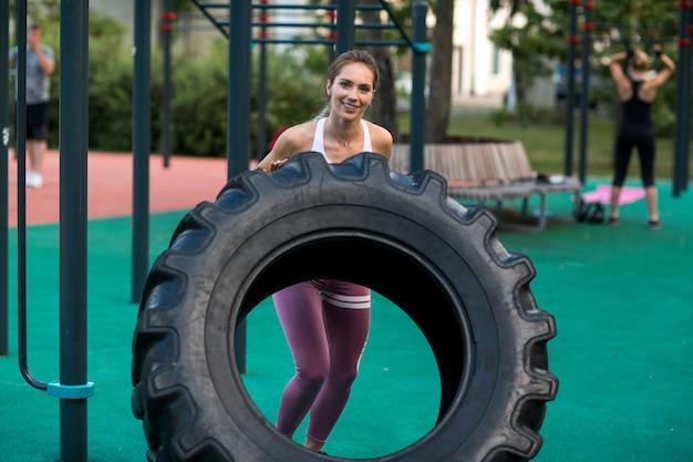 Молодая женщина тренируется с шинами на открытой площадке. тренажерный зал на открытом воздухе