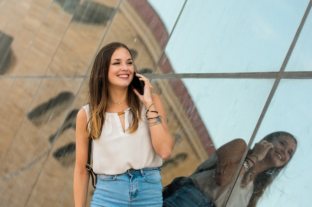 Young woman is using her smartphone, there is a mirror behind her