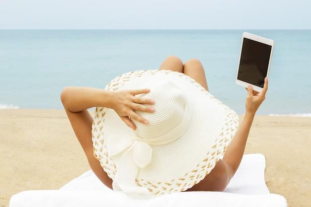Молодая женщина использует планшетный пк на пляже