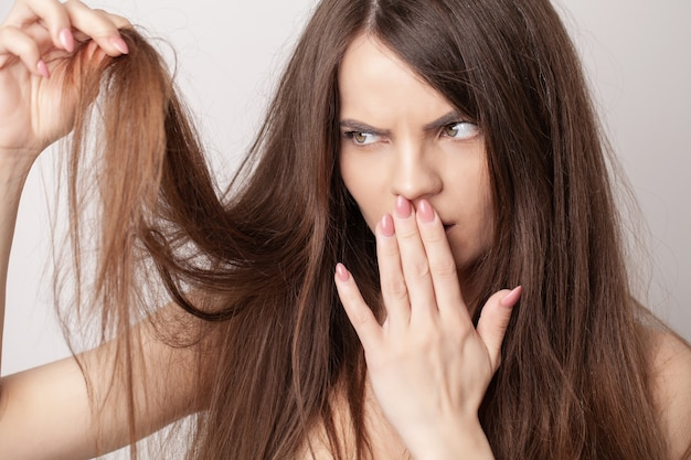 Молодая женщина очень расстроена из-за выпадения волос.