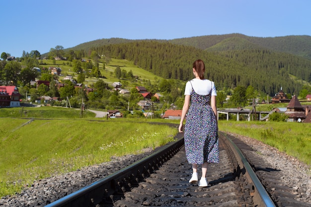 Young woman is walking along the railway tracks.