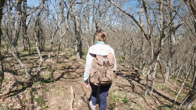 若い女性はバッグパックを持って森の中を歩いています。春の罪の日に屋外で森を散歩し、森の中を歩いているアクティブで健康的な旅行者です。