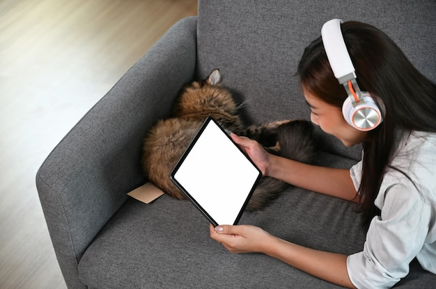 A young woman is watching a movie on a tablet device with empty screen while lying on couch.