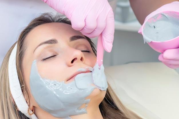 Молодая женщина носит серую альгинатную маску
