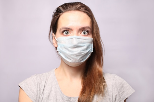 A young woman is wearing a respiratory protective mask. the chewing gum has turned gray with fear and looks with big frightened eyes. flu epidemic, dust allergy. coronavirus 2019 ncov.