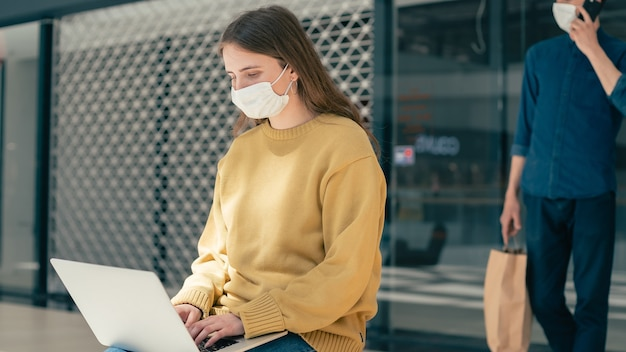 Young woman is working on a laptop while sitting outside a city building. pandemic in the city
