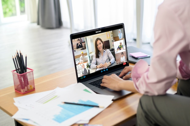 Young woman is working with her computer screen while business meeting through video conferencing application .