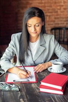 Молодая женщина пишет планы в тетради за столом в современном интерьере кафе.