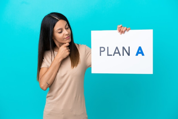 Young woman over isolated background holding a placard with the message plan a and thinking