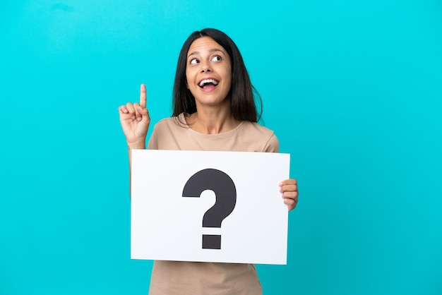 Young woman over isolated background holding a placard with question mark symbol and thinking