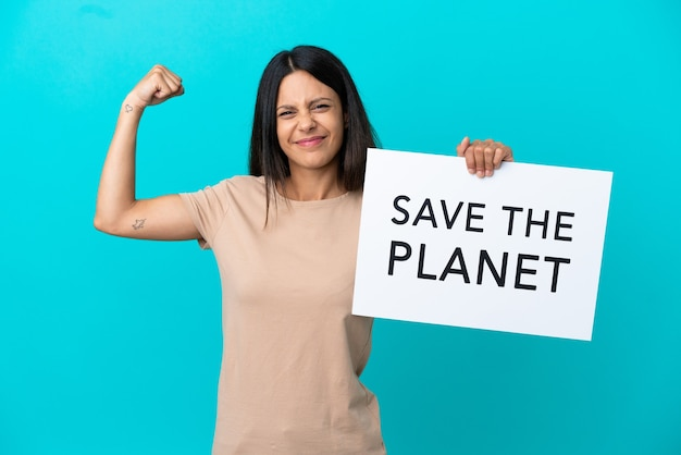 Young woman over isolated background holding a placard with text save the planet and doing strong gesture