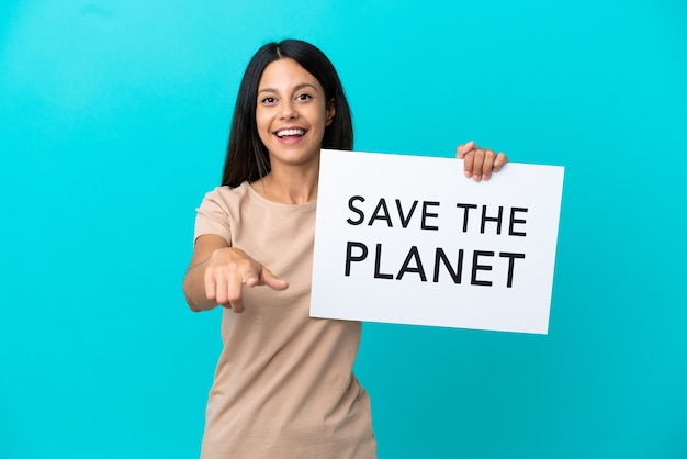 Young woman over isolated background holding a placard with text save the planet and pointing to the front