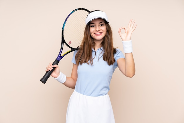 Young woman isolated on beige playing tennis and making ok sign
