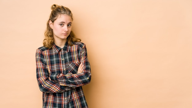 Young woman isolated on beige wall unhappy looking in front with sarcastic expression