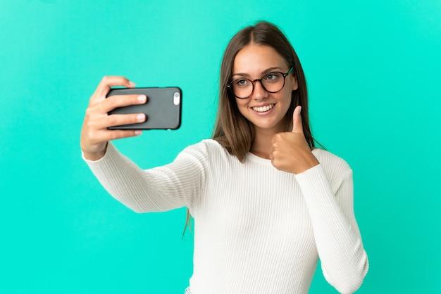 若い女性が携帯電話で自分撮りをする青い背景を分離