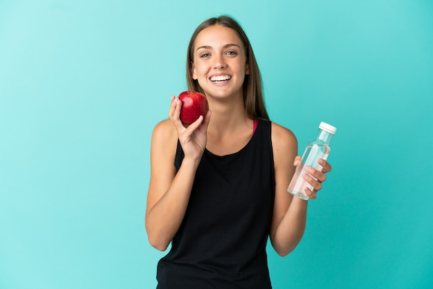 Young woman over isolated blue background with an apple and with a bottle of water