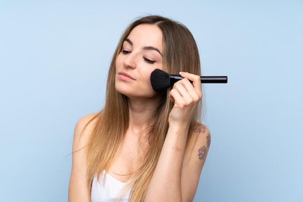 Young woman over isolated blue background with makeup brush