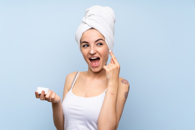 Young woman over isolated blue background with moisturizer