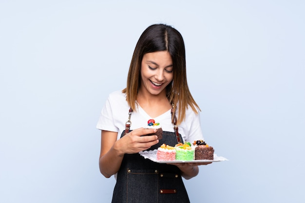 Young woman over isolated blue holding mini cakes and surprised