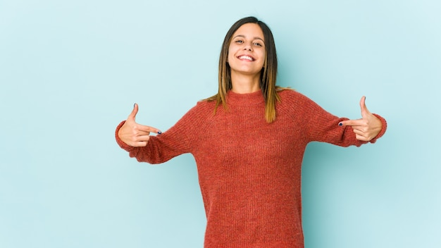 Young woman isolated on blue points down with fingers, positive feeling.
