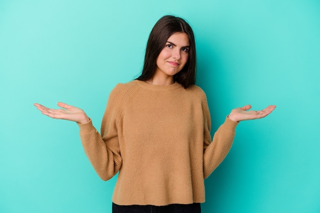 Young woman isolated on blue wall doubting and shrugging shoulders in questioning gesture