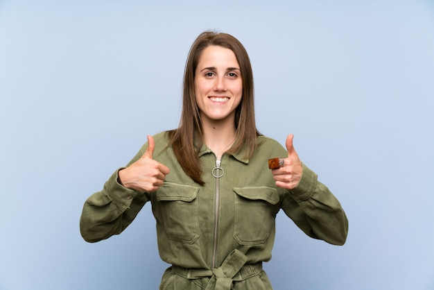 Young woman over isolated blue wall giving a thumbs up gesture