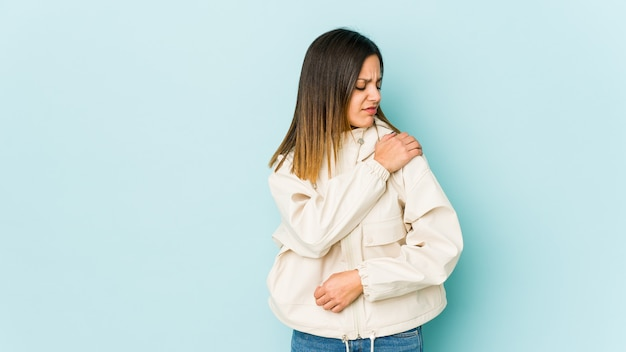 Young woman isolated on blue wall having a shoulder pain