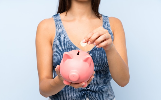 Young woman over isolated blue wall holding a big piggybank