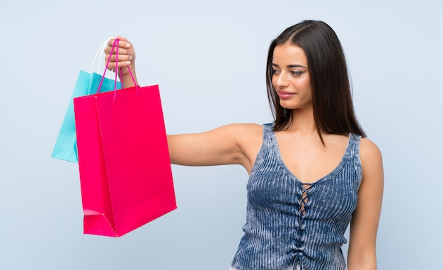 Young woman over isolated blue wall holding a lot of shopping bags