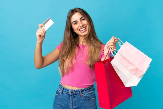 Young woman over isolated blue wall holding shopping bags and a credit card