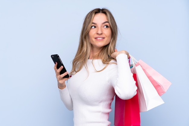Young woman over isolated blue wall holding shopping bags and a mobile phone