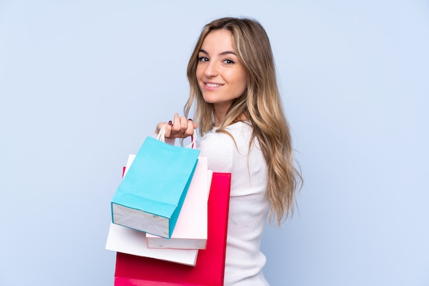 Young woman over isolated blue wall holding shopping bags and smiling