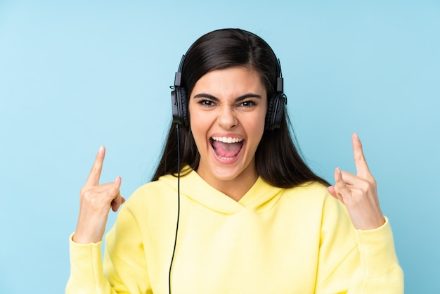 Young woman over isolated blue wall listening music making rock gesture