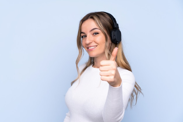 Young woman over isolated blue wall listening music and with thumb up
