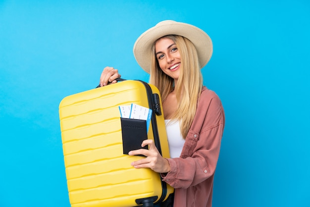 Young woman over isolated blue wall in vacation with suitcase and passport