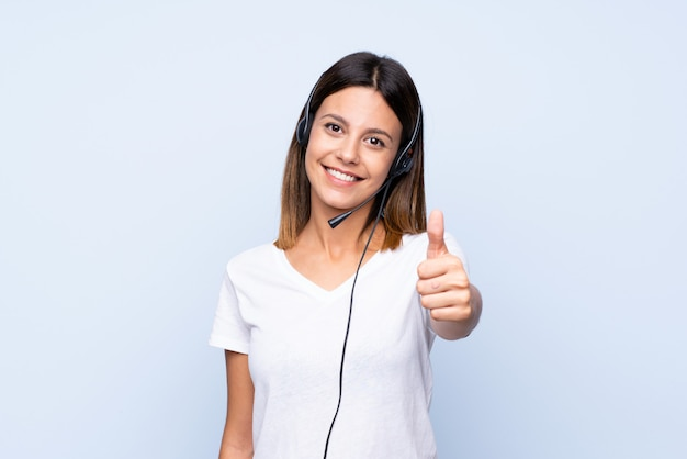 Young woman over isolated blue  working with headset with thumb up