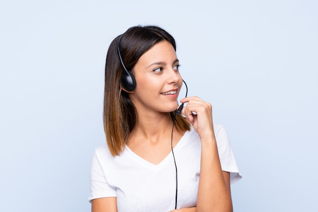Young woman over isolated blue working with headset