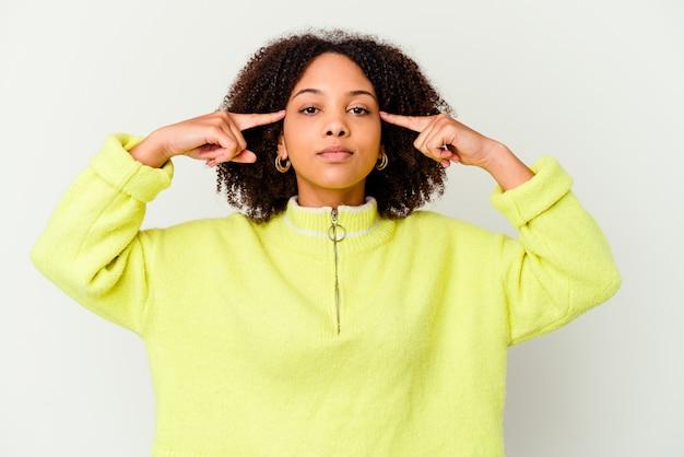 Изолированная молодая женщина сосредоточилась на задаче, держа указательные пальцы на голове