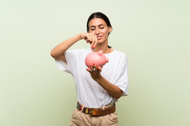 Young woman over isolated green wall holding a big piggybank