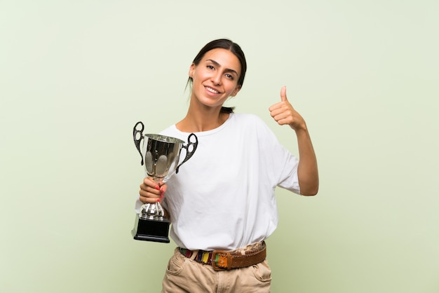 Young woman over isolated green wall holding a trophy