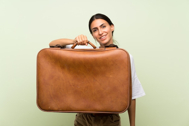 Young woman over isolated green wall holding a vintage briefcase