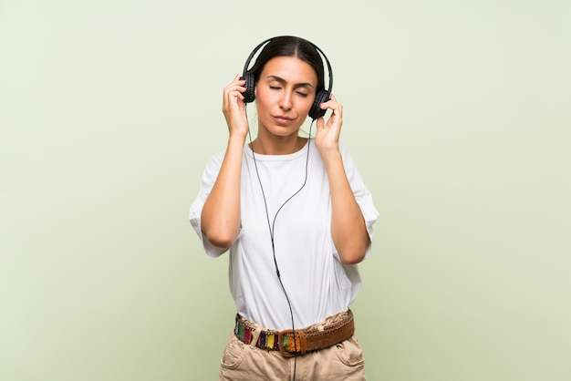 Young woman over isolated green wall listening to music with headphones