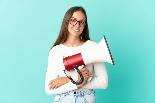 Молодая женщина изолирована, держа мегафон и улыбается