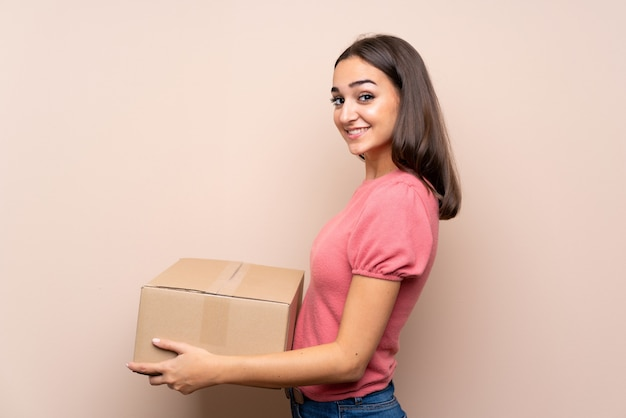 Young woman over isolated holding a box to move it to another site