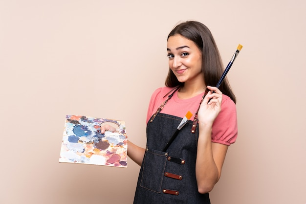 Young woman over isolated  holding a palette