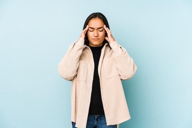 青に触れるこめかみに孤立し、頭痛を抱えている若い女性。