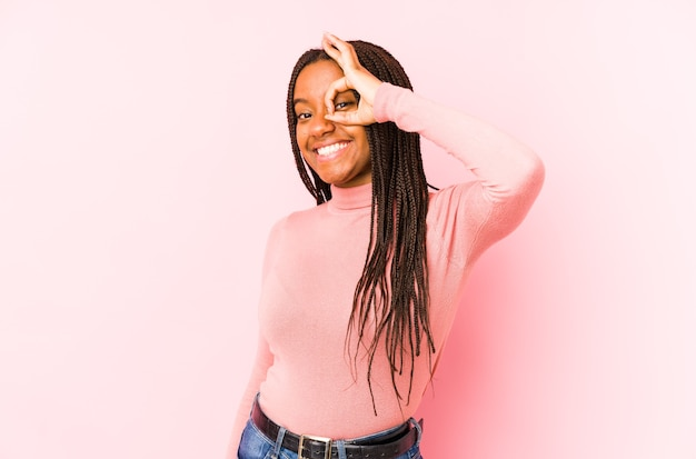 Молодая женщина, изолированная на розовой стене, взволнована, держа на глазах жест в порядке