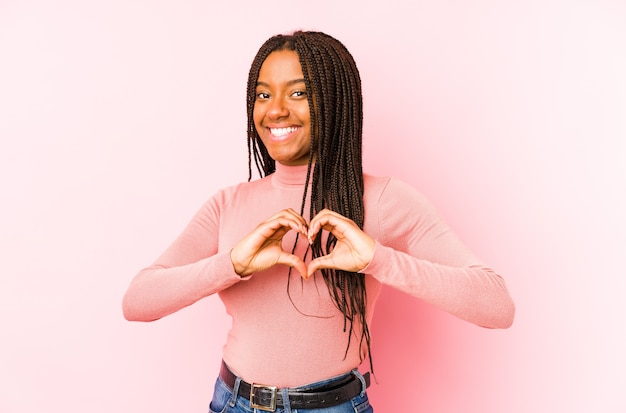 Молодая женщина изолирована на розовой стене улыбается и показывает руками форму сердца