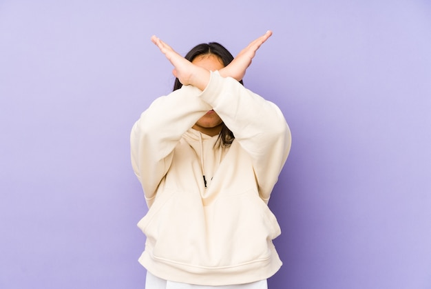 Молодая женщина, изолированные на фиолетовом пространстве, скрещенными двумя руками, концепция отрицания.
